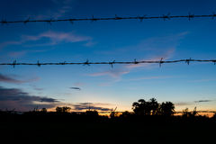 Silhouettes of Barbed wire on blurred sunset background Royalty Free Stock Photography