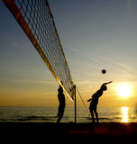 Silhouettes of beach volleyball players. At sunset Royalty Free Stock Photos