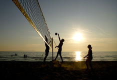Silhouettes of beach volleyball players. At sunset Royalty Free Stock Image