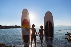 Silhouettes of beautiful couple with sup serf and paddle at the ocean. Silhouette of beautiful couple with sup serf and paddle at the ocean Stock Image