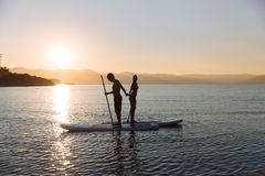 Silhouettes of beautiful couple with sup serf and paddle at the ocean. Silhouette of beautiful couple with sup serf and paddle at the ocean Stock Photography