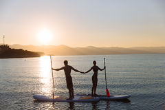 Silhouettes of beautiful couple with sup serf and paddle at the ocean. Silhouette of beautiful couple with sup serf and paddle at the ocean Royalty Free Stock Images