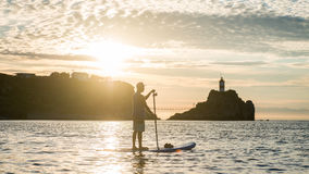 Silhouettes of beautiful couple with sup serf. Silhouettes with sup surfing and paddle on the sea of Japan Stock Photo