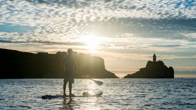 Silhouettes of beautiful couple with sup serf. Silhouettes with sup surfing and paddle on the sea of Japan Stock Images