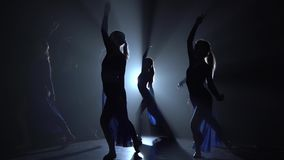 Silhouettes of beautiful slim figures dancing on black background, studio. Flexible young ballerinas in light dresses are dancing elements of a modern ballet in stock footage