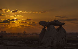 Silhouettes of Big Stones on orange sunsets cloudscape background. With citys silhuettes Royalty Free Stock Photography