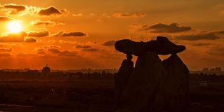Silhouettes of Big Stones on orange sunset cloudscape background Royalty Free Stock Images