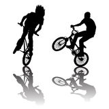 Silhouettes of bikers doing tricks Stock Photo