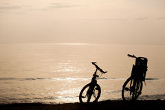 Silhouettes of bikes on the coast Stock Images