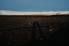 Silhouettes on a black sand beach. Silhouette of two people on a black sand beach in Iceland at sunset Stock Image