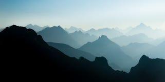 Silhouettes bleues et cyan spectaculaires de gammes de montagne Le sommet croise évident Photographie stock libre de droits