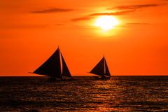 Silhouettes of boats against a red sunset sky Royalty Free Stock Photo