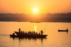 Silhouettes of Boats with pilgrims during amazing sunset on the Holy Ganges river, Varanasi. Silhouettes of Boats with pilgrims during amazing sunset on the stock photos