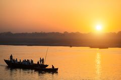 Silhouettes of Boats with pilgrims during sunset on the Holy Ganges river in Varanasi stock images