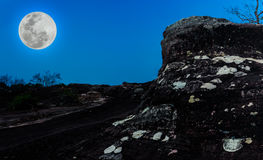 Silhouettes of boulders against blue sky and beautiful full moon Stock Photos