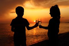 Silhouettes of boy and girl with glasses on sunset Stock Images