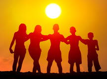 Silhouettes of boys and girls hugging on the beach. On sunny summer day Stock Images