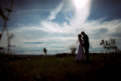 Silhouettes of bride and groom on the background field sky Stock Photography