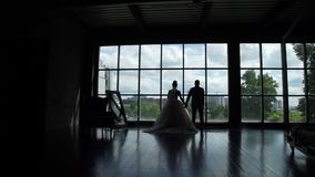 Silhouettes of newlyweds in front of big window. Silhouettes of bride and groom enjoying view from their new apartments. They are standing in front of big stock video footage