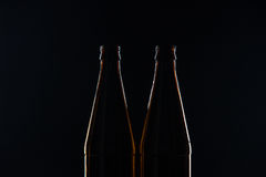 Silhouettes brown glass bottles for beer on a black background Royalty Free Stock Photography