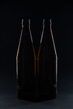 Silhouettes brown glass bottles for beer on a black background Stock Photo