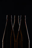 Silhouettes brown glass bottles for beer on a black background Stock Photos