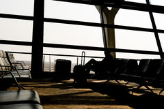 Silhouettes of business man at airport; waiting at the plane boarding gates. Royalty Free Stock Image