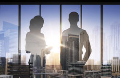 Silhouettes of business partners over city office Royalty Free Stock Images