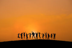 Silhouettes of Business People with Arms Raised Stock Images