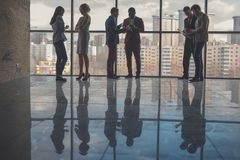 Silhouettes of business people in conference room. Silhouettes of business people in a conference room Stock Photo