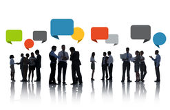 Silhouettes of Business People Discussing with Speech Bubbles Stock Photo