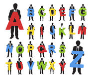 Silhouettes of Business People Holding Alphabet Texts Concept.  Royalty Free Stock Images