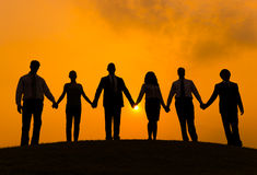Silhouettes of Business People Holding Hands Outdoors Stock Images