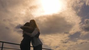 Silhouettes of business women who rejoice in success and victory. two girls on the roof hold hands and exult. Goal stock footage