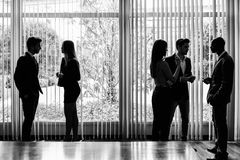 Silhouettes of businesspeople interacting background business ce Stock Images
