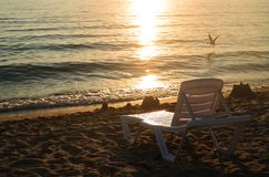 Silhouettes of chaise lounges on the beach of the sea, sunset. Chaise lounge on the beach at sunset royalty free stock photography