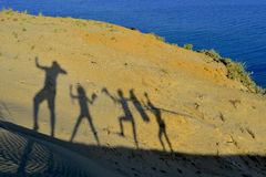 Silhouettes of cheerful happy family enjoying. Shadows of cheerful happy family enjoying hiking the sand dunes of a beautiful island with blue ocean view Royalty Free Stock Photos
