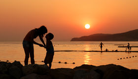 Silhouettes of child and his mother against sunset. Silhouettes of child and his mother against the orange sunset at sea royalty free stock photo