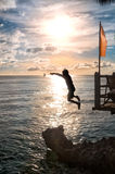 Silhouettes of child jumping in sea. Over sunset Royalty Free Stock Image