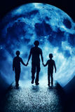 Silhouettes of children and adult are before the moon Royalty Free Stock Images