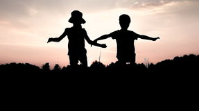 Silhouettes of children jumping off a cliff at sunset. Little boy and girl jump raising hands up high. Brother and sister having fun in summer. Friendship royalty free stock photography