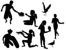 Silhouettes of children playing on the beach. Children on the beach with sea creatures and birds Royalty Free Stock Images