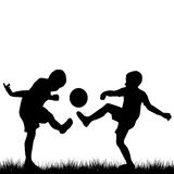 Silhouettes of children playing football Stock Photo