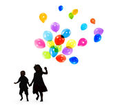 Silhouettes of Children Playing and Holding Balloons Stock Images