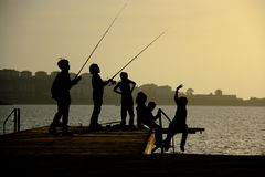 Silhouettes of childs on pier catching fish. Silhouettes of childs having fun ad catching fish on pier at summer evening Stock Image