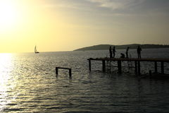 Silhouettes of childs on pier catching fish. Silhouettes of childs having fun ad catching fish on pier at summer evening stock photography