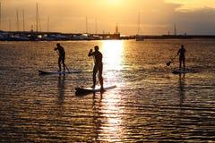 Silhouettes comiques de paddler au coucher du soleil Image libre de droits