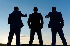 Silhouettes of company leaders standing on sunset sky background. Board of executives look at their worksite and new goals. Businessmen figures in formal suits royalty free stock photos