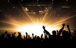Silhouettes of concert and bright stage lights background. Hands up, toned, bright stage lights background royalty free stock image
