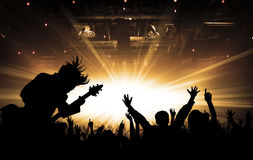 Silhouettes of concert and bright stage lights background. Hands up, toned, bright stage lights background royalty free stock photography
